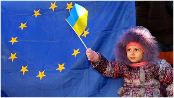 The beginning of the Revolution of Dignity. A girl holds the Ukrainian flag during a protest
